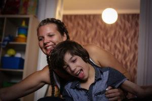 mozgáskorlátozott gyerek a segítőjével tornázik